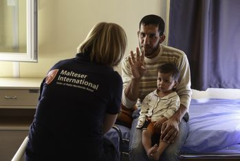 A staff member talks to a Syrian refugee who is being treated in the clinic. Photo: Kerem Yucel