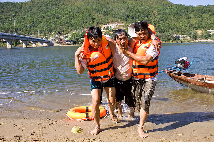 In a community drill, villagers show how to evacuate the weak and injured by boats.
