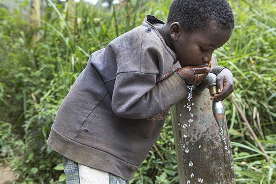 A Congolese boy enjoys clean water coming from the new water tap at the health center.