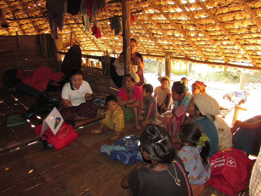 Hto Lwe Htoo speaks to the members of a mother and child group about birth and pregnancy.