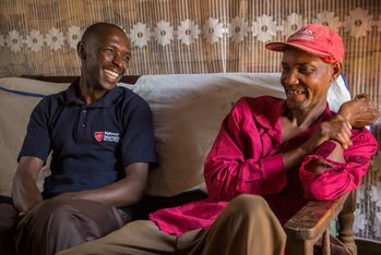 "Kimani (left) during a home visit to a TB patient. He is a so-called ""community worker,"" who connects villagers with the local health care structures. Photo: African Visuals Media"